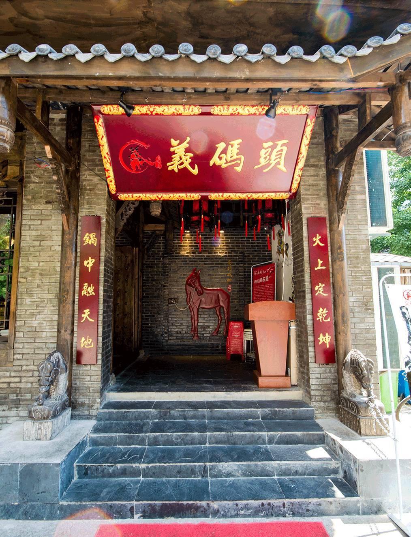 两层木质结构古朴建筑,门口挂着小红灯笼,有点像武林外传里的同福客栈